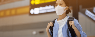 Coronavirus & ecommerce: girl at the airport wearing a mask