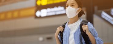 Coronavirus & ecommerce: girl at the airport wearing a mask